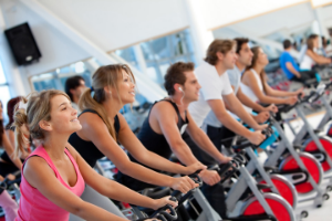 Men and women sitting on exercise bikes in spinning class