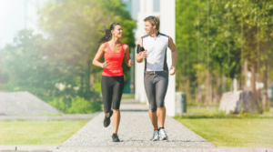 a man and woman running along a path to improve health